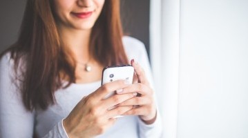 Young female holding her phone and looking at the screen intently