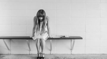 Young female crouched over a bench looking sad and in despair
